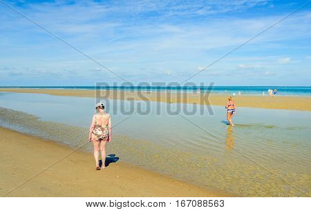 An older woman with bathing suit and cap looking at the tide line on a quiet part of the Dutch North Sea beach. It's a sunny day in the summer season.
