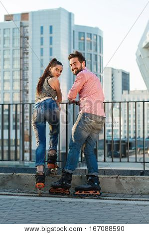 Couple on rollerblades looking back. People on building background. Ride with us.