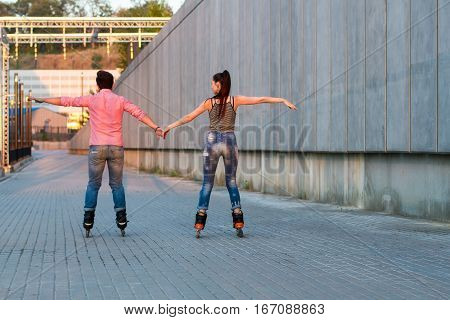 Couple on rollerblades holding hands. Back view of inline skaters. Be free like birds.
