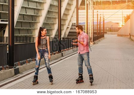 Young couple inline skating. Girl on rollerblades smiling. Cheerful mood and good impressions.