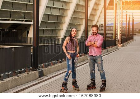 Young couple wearing inline skates. Man with crossed arms standing. We live by sport.