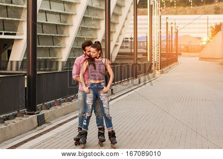 Couple on rollerblades standing. Man behind woman. Love and support each other.