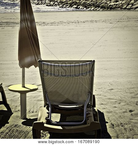 Beach Umbrella and Sun Bed in the Low Season Vintage Style Toned Picture
