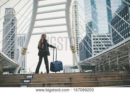 Businesswoman Dragging A Suitcase. And Walking Through The Corridor During Rush Hour In The City.