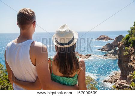 Young couple enjoying the view of the Costa Brava coast and the sea at the Tossa de Mar Catalonia Spain.