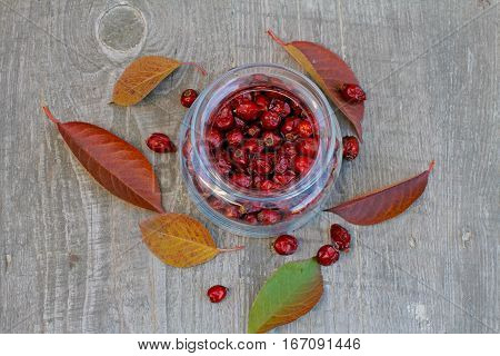 Rosehips in a glass jar on a wooden background with leaves and berries