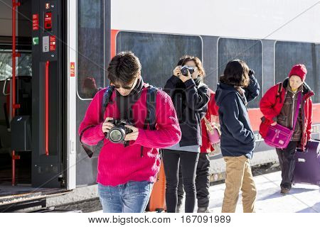 HALLSTATT, AUSTRIA - JANUARY 10, 2017 : Group of Chinese Tourists at Train Station,  Coming to Hallstatt Across the Mountain Lake by Boat - Water Bus