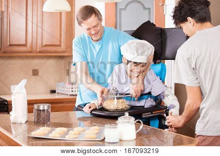 Disabled boy standing in stander laughing as he makes chocolate chip chip cookies with father and brother in kitchen