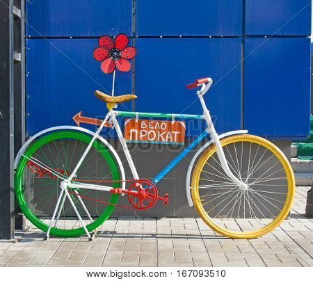 Colorful bicycle with Bike Rental sign and flower
