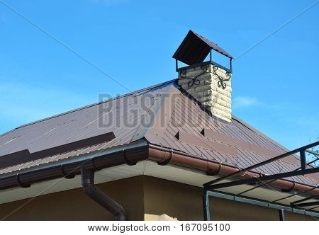 Closeup on new house rain gutter system and roof protection from snow board (Snow guard) on house roofing and wall construction