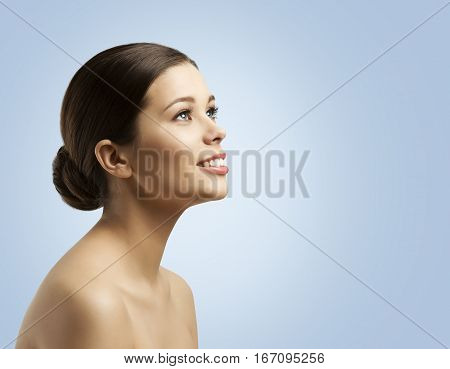 Woman Face Side View Bun Hair Fashion Model Beauty Makeup and Hairstyle over Blue