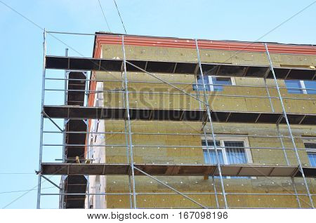 Exterior house wall heat insulation with mineral wool building under construction. Insulation is defined as a material or combination of materials which retard the flow of heat.