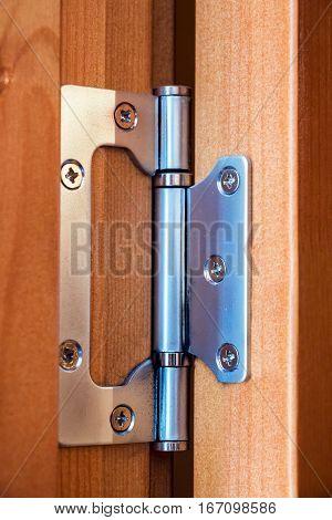 Steel hinge on the wooden door closeup