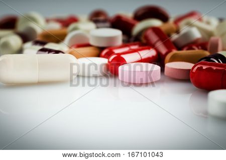 Medical theme. Plenty of red and other pills and capsules. Closeup
