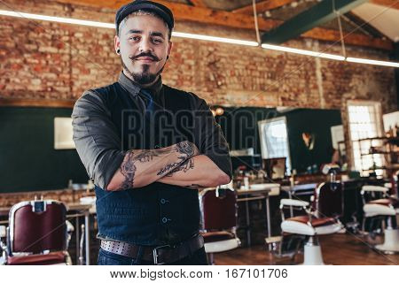 Portrait of handsome young man standing at barber shop. Stylish hairstylist standing in his salon with his arms crossed.