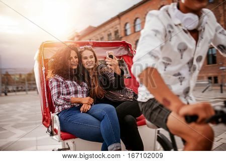 Shot of female friends taking selfie on tricycle ride. Young women riding on tricycle bike and taking self portrait.
