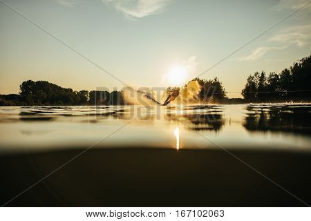 Water surface level shot of wakeboarder skiing on lake at sunset.