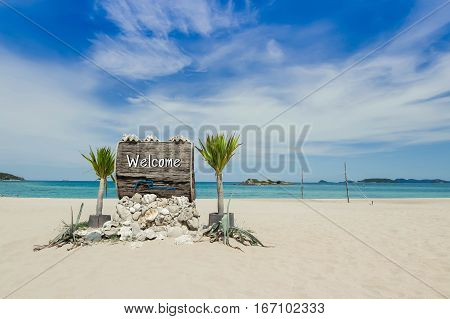 Welcome text on wooden sign on the beach with beach volleyball court