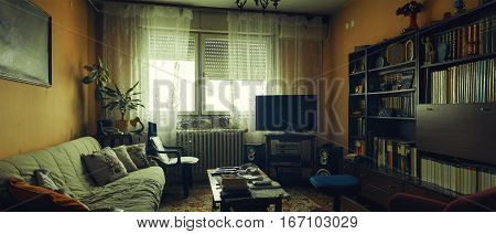 Lifestyle of an older people interior of a living room with lot of books old furniture and some audio equipment.