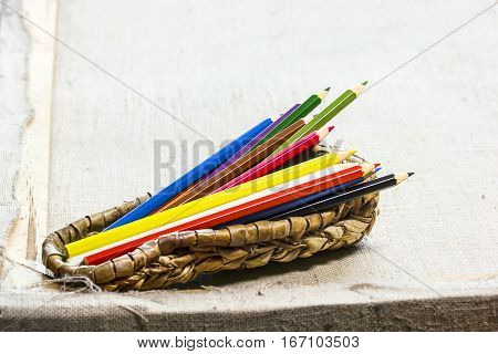 Pencils in a wicker bast on a gray canvas