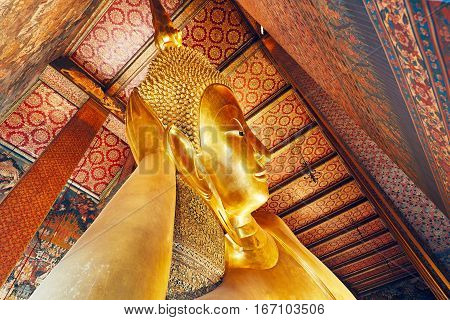 Golden statue of the Reclining Buddha in Wat Pho (Pho Temple) in Bangkok Thailand.