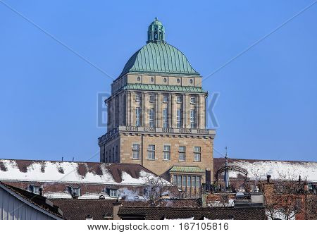 Zurich, Switzerland - 27 January, 2017: the tower of the main building of the the University of Zurich rising above roofs of the historical part of the city. The University of Zurich is the largest university in Switzerland, founded in 1833.