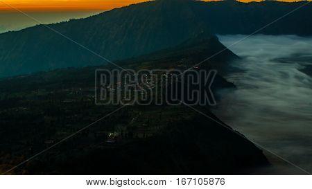 Sunrise at volcano Mount Bromo, sun beyound horizon, clouds swimming around, early