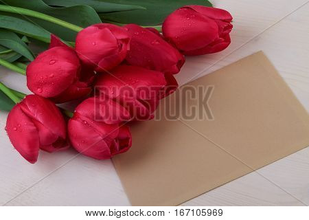 Red tulips and paper sheet still life