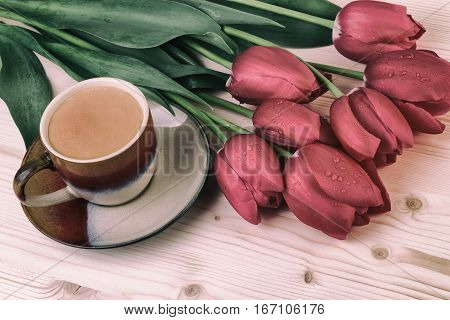 Cup of coffee with red tulips on wooden table. Coffee in vintage style