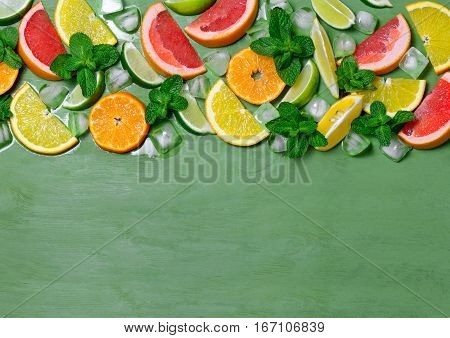 Various citrus fruits mint and ice cubes view from above. Summer cooler drink concept