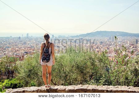 Young girl tourist with a backpack looking at a panoramic view of the city Barcelona Spain. poster