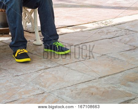 closeup man legs wear blue jeans pants and difference color sneakers shoes space for text