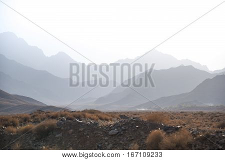 stone desert with dry plant and layers of mountain under clear white sky majestic landscape in Iran
