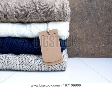 Pile woolen knitted warm sweater on rustic background