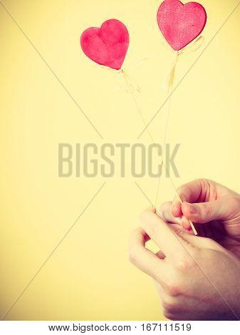 Romance affection valentines gift concept. Two hands with love symbols. Hearts on poles held by people.