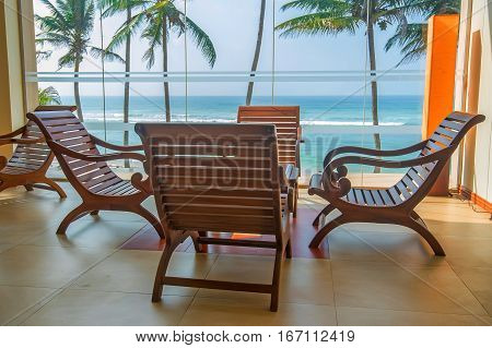 Detail of interior in colonial style of lounge in tropical resort with view of palms and ocean