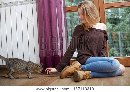 Smiling woman holding and pampering cat indoors