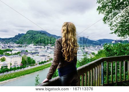 Girl looking at  Salzach River in Salzburg, Austria. Famous place Unesco Heritage Festung Hohensalzburg, Salzburger Land, Europe