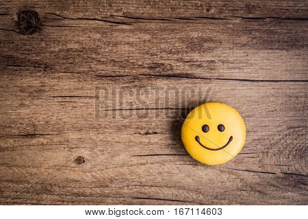 Glazed cookies in the shape of a smiley on a wooden background