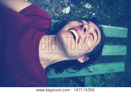 Tickled Woman Laughing On A Bench