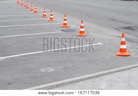 Traffic cone on the road. Closed car parking lot with white mark and traffic cone on street used warning sign on road