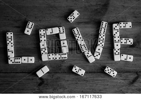 Love sign of white domino pieces on bright brown wooden background (bithday, valentines day, wedding) on black and white background