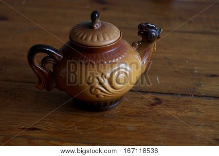 Beautiful brown clay teapot in shape of rooster bird close up isolated on wooden table on brown background