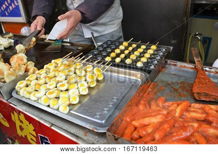 A vendor in Beijing, China sells street food of quail eggs on a skewer.