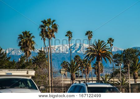 Highest mountain peaks behind beach town of Ventura covered in snow after series of winter storms.