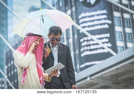 Arabic Businessman Looking Tablet With His Bodyguard On Cityscape Background