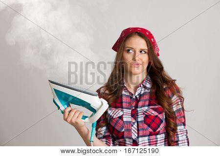 Unhappy woman ironing with steam blowing in the air