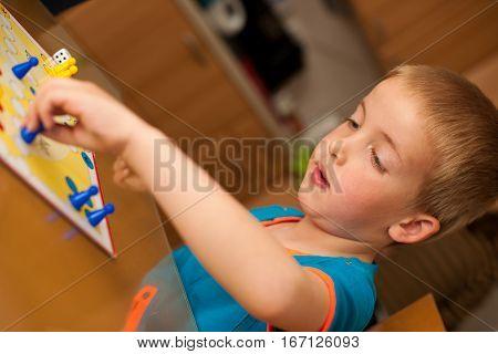 young boy plays ludo game on a table in livingroom