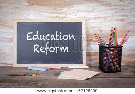 Education Reform text on a blackboard. Old wooden table with texture.