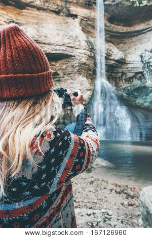 Woman photographer taking photo of waterfall Travel Lifestyle adventure concept active vacations into the wild harmony with nature